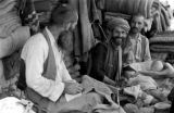 Afghanistan, merchants at stand in Kābul market