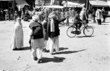Afghanistan, Kābul street scene with woman in burqa and man on bicycle