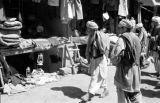 Afghanistan, men reviewing goods in Kābul market
