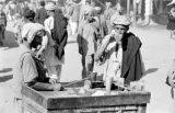 Afghanistan, customer drinking vendor's iced beverage at Kābul market
