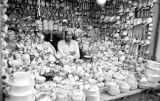 Afghanistan, pottery vendor surrounded by goods at Kābul market