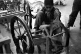 Afghanistan, boy using spinning wheel at cotton mill in Pol-e Khomri