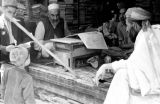 Afghanistan, merchant reading paper at stand in Kābul market