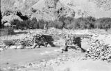 Afghanistan, men crossing bridge over mountain stream at Dowshi
