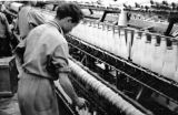 Afghanistan, factory worker using machine at cotton mill in Pol-e Khomri