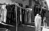 Afghanistan, woman wearing burqa walking past Western-style dresses displayed in Kābul