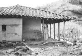 Colombia, woman on porch of upper Finca Sanchez farmhouse in Antioquia department