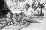 Venezuela, woman kneeling next to four babies on grass mat in Maracaibo