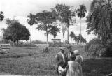 Colombia, Don Carlos, Harriet Platt, and others talking near gate at Hacienda El Hatico