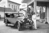 Colombia, chauffeur, Luis Eduardo Correa, posing with Packard car at corner gas station in Cali