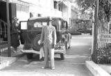 Guyana, chauffeur and Harriet Platt posing with car in front of Park Hotel in Georgetown