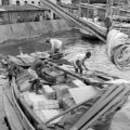 Brazil, men loading and securing materials on boat in Salvador