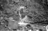 Bolivia, gold miner taking shower under waterfall in La Paz