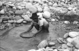 Bolivia, Indian man panning for gold in Tipuani River in La Paz