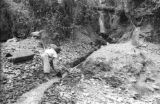 Bolivia, worker digging sluice where waterfall meets Tipuani River in La Paz