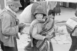 Peru, woman carrying infant at Huancayo marketplace