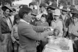 Peru, street vendor presenting items to spectators at Huancayo market
