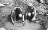 Bolivia, miners washing gold-bearing mud from pool in La Paz