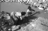 Bolivia, man in La Paz shoveling mud from stream to woman to sift for gold