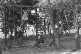 Paraguay, girls swinging on play structure in Hutterite community