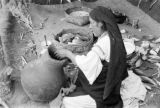 Ecuador, woman making pottery outdoors