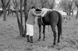 Argentina, man saddling horse at Pato game