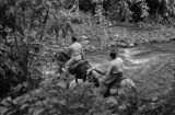 Colombia, men crossing stream on horses at Muzo Emerald mines