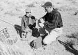 Peru, man and boy preparing fishing poles at Lake Titicaca