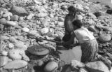 Bolivia, woman and girl panning for gold from edge of Tipuani River