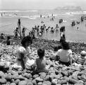 Peru, women and children at beach in Lima