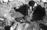 Bolivia, close-up of woman in La Paz mining gold from mud in shallow hole