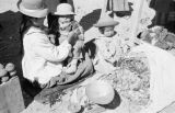 Peru, woman with children weighing coca leaves at Juliaca market