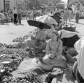Paraguay, girl sitting with merchants at market in Asunción
