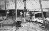 Paraguay, men stacking lumber at Hutterite community sawmill