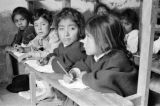 Ecuador, row of children doing assignments in classroom
