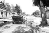 Brazil, children standing around parked car in Santo Antônio