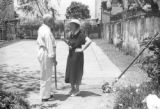 Brazil, Harriet Platt & Mr. Howe talking near tennis court in Ilhéus