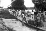 Peru, men with baskets of produce next to railroad tracks in Iquitos