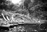 Peru, children and woman doing laundry in canoes at river's edge