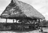 Peru, boy sitting outside thatched roof stilt house