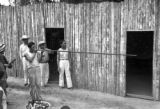 Peru, man demonstrating use of blowgun for hunting