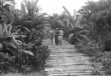 Peru, people walking on pedestrian bridge in village