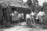 Peru, people standing outside thatched roof hut