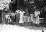 Peru, family portrait in front of thatched roof hut in Iquitos