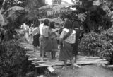 Peru, women walking on pedestrian bridge in village