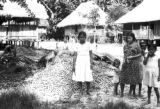 Peru, women and children standing by tagua nut pile in village