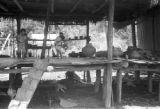 Peru, sick child and family on porch of stilt house