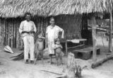 Brazil, family outside hut