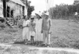 Brazil, family outside thatched roof hut