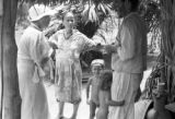 Brazil, Harriet Platt speaking with family outside hut